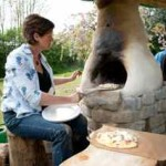 Kate cooks pizzas in a cob pizza oven for lunch on our workshop