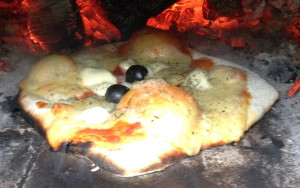 cooked pizza in oven by embers